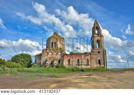 Ruined Church With A Bell Tower Overgrown With Grass Against A Cloudy Sky, Side View
