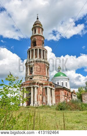 Abandoned Bell Tower With A Cross In The Background, Made Of Bricks With Columns Against The Sky, Tr