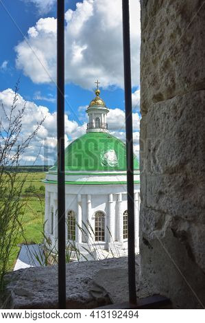 Part Of The Restored Church With A New Dome Against A Cloudy Sky, View Through The Grate, Close-up