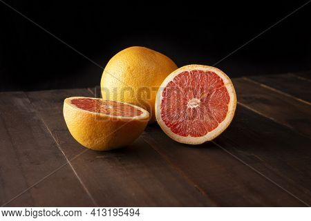 Half Cut Ripe Grapefruit And Whole Grapefruit On Brown Rustic Wooden Table With Black Background