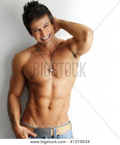 Sexy smiling shirtless male model flirting against white background