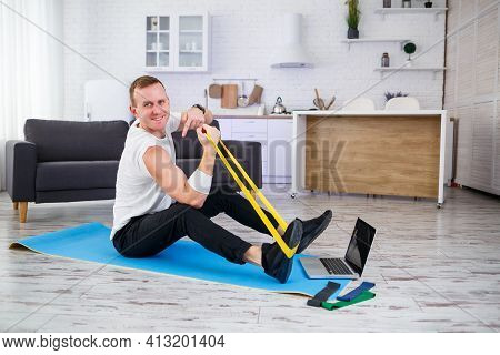 Online Training. Man Doing Exercise With Rubber Bands At Home, Free Space. Doing Sports At Home