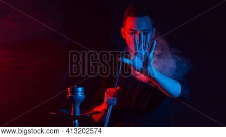 Male Smoker Smokes A Hookah In A Shisha And Lets Out A Cloud Of Smoke