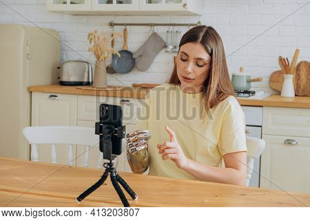Lady With Shiny Bionic Prosthesis Shooting Video In Kitchen