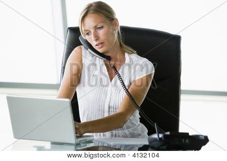 Zakenvrouw zitten In kantoor met een Laptop op telefoon
