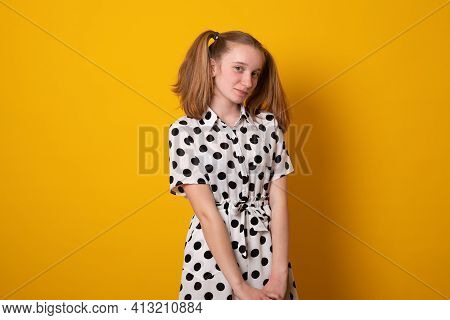 Cute Girl With A Two-ponytail Hairstyle Smiles With Braces On A Yellow Background. Teenager Girl Wit