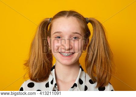 Cheerful Girl With A Two-ponytail Hairstyle Smiles With Braces On A Yellow Background. Teenager Girl