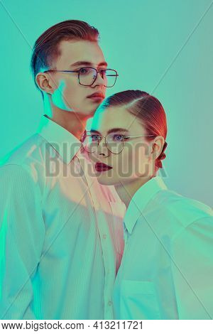 Fashion girl and guy posing in white shirts and modern sunglasses are pose at studio in turquoise and red lighting. Optics, fashion.