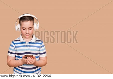 Cheerful Young Boy Listening To The Music In Headphones And Mobile Phone. Smiling Boy Using Smartpho
