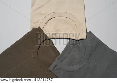 Folded Jumpers On A White Isolated Background. Colored Stylish Clothes Are Laid Out In A Circle. Bei