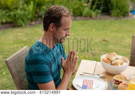 Caucasian man with hands in prayer saying grace before eating meal with family in garden. three generation family celebrating independence day eating outdoors together.