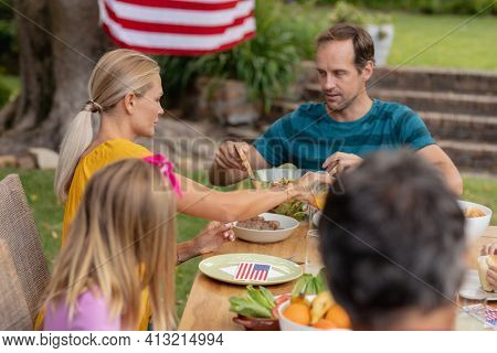 Caucasian man serving family before eating meal together in garden. three generation family celebrating independence day eating outdoors together.
