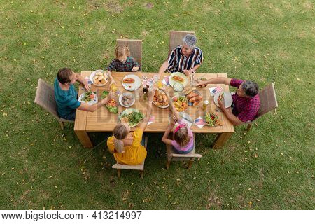 Overhead view of caucasian three generation family at table eating meal in garden making a toast. three generation family celebrating independence day eating outdoors together.