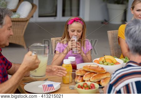 Smiling caucasian girl drinking lemonade sitting with family eating meal together in garden. three generation family celebrating independence day eating outdoors together.