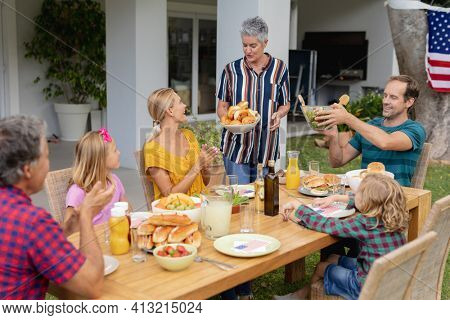 Smiling caucasian senior woman serving family before eating meal together in garden. three generation family celebrating independence day eating outdoors together.