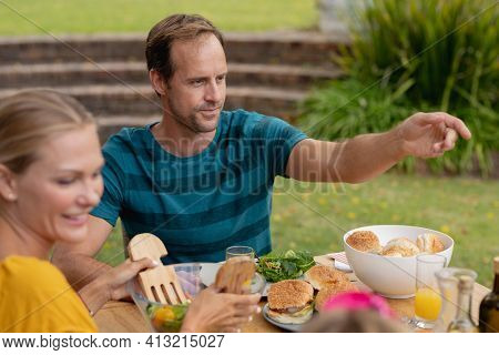 Smiling caucasian gesturing across table eating meal with family in garden. family celebrating independence day eating outdoors together.