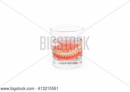 A Denture In A Glass Of Water. Dental Prosthesis Care. Full Removable Plastic Denture Of The Jaws. T