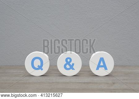 Q And A Letter On White Circle Shape On Wooden Table Over White Wall Background, Frequently Asked Qu