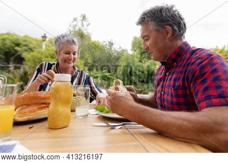 Smiling caucasian senior man holding hamburger eating meal with wife in garden. family celebrating independence day eating outdoors together.