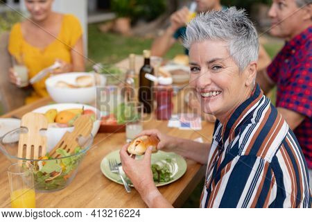 Portrait of smiling caucasian senior woman holding hotdog at table with family having meal in garden. three generation family celebrating independence day eating outdoors together.