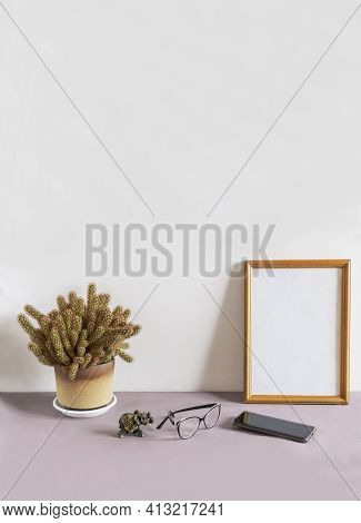 On A Table Against A White Wall Is A Wooden Photo Frame And A Potted Cactus Flower. Next To It Are G
