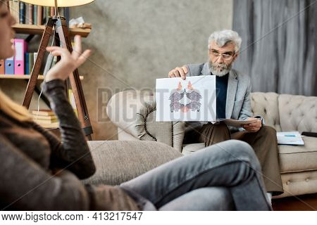 Psychotherapist Showing Rorschach Inkblot Test Pictures To Young Caucasian Woman During Session In O