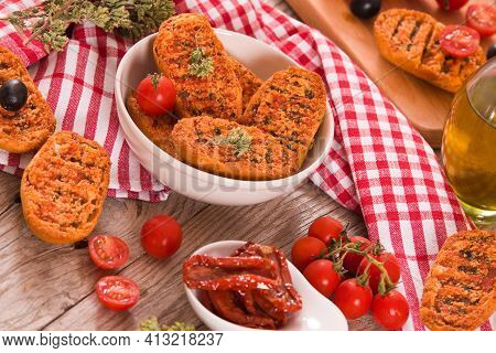 Toasted Bread With Tomato And Oregano On Wooden Table.