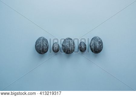 5 Blue Gray Marble Painted Easter Eggs On A Blue Background