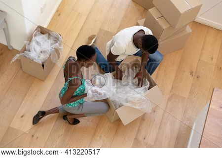 African american couple moving house unpacking boxes together. staying at home in isolation during quarantine lockdown.