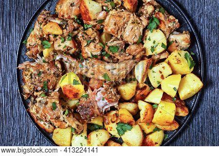 Conejo Al Ajillo, Braised Rabbit With Potatoes, Garlic, White Wine, Salt, And Olive Oil On A Black P