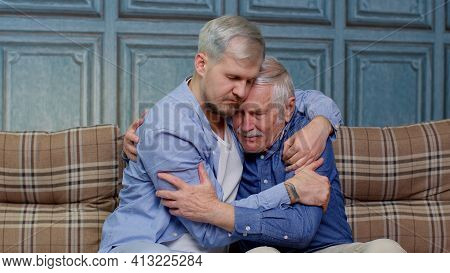 Handsome Adult Caucasian Man Comforting His Depressed Senior Father, Asking About Problems. Son Hugg
