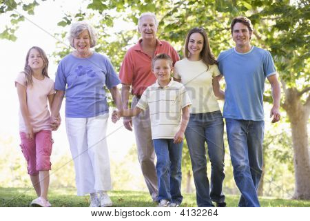 Extended Families Walking In Park Holding Hands And Smiling