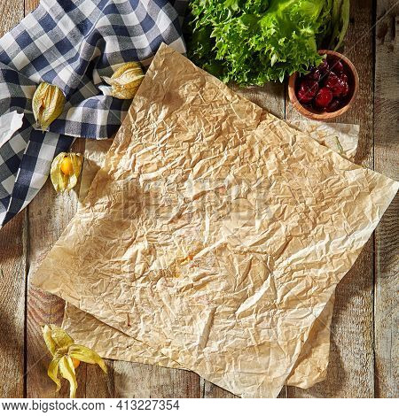 Baking paper with food ingredients. Wooden table at kitchen with baking utensil and fresh vegetables. Crumpled parchment or baking paper as a creative copy space. Top view