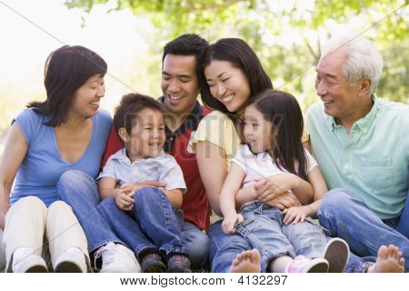 Extended Families Sitting Outdoors Smiling