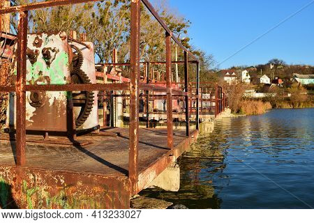 Old Iron Dam On The River. Rusting Operational Gear On Old Dam Infrastructure. Old Rusty Gears From