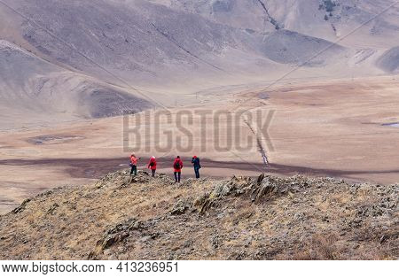 Tourists Wearing Red And Blue Clothes Having Rest On The Top Of Mountain. Mountain Valley Landscape.