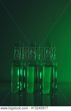 Biotechnology And Science. Medicine And Pharmacology Concept.glass Transparent Ampoules Set In Green