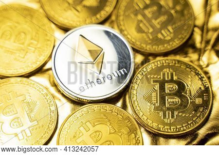 Gold Ethereum Coins Among Bitcoins On A Golden Background. Trading On The Cryptocurrency Exchange. C