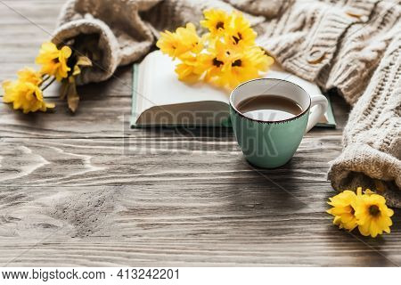 Spring Morning Coffee. A Cup Of Coffee On A Wooden Table And A Warm Sweater Against A Background Of
