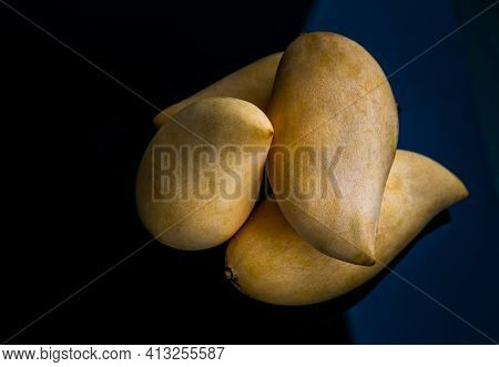 Ripe Yellow Barracuda Mango Fruit (nam Dok Mai) On Black Table Background. Tropical Healthy Fruit Ba