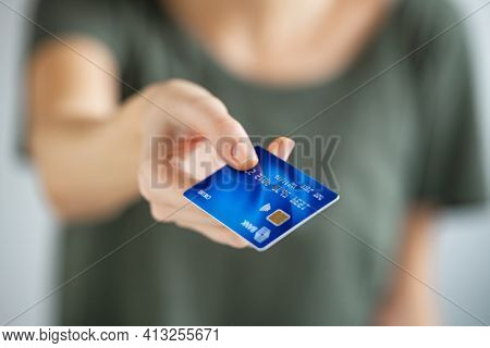 Close up of young woman hand holding credit card. Woman extending hand to give credit card to cashier. Close up of a girl paying with blue creditcard.