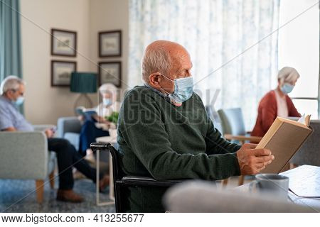 Senior man wearing face mask and reading a book at nursing home. Old disabled man sitting on wheelchair reading book during covid-19 pandemic. Elder wearing surgical mask and reading during lockdown.