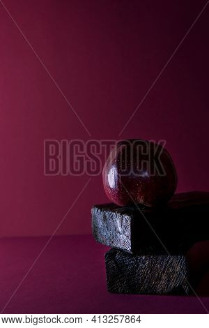 A Red Apple On A Maroon Background With Space For Text Is A Concept Of Simplicity And Elegance. The