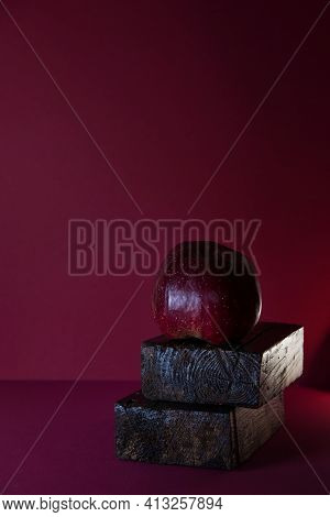 Red Apple On A Dark Red Background With Space For Text. The Concept Of Simplicity And Grace. Adverti