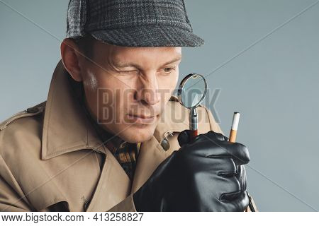 Male Detective Exploring Cigarette Stub With Magnifying Glass On Grey Background