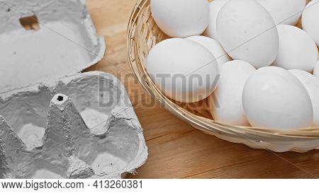 Egg Tray And Wicker Basket With Plenty Of White Eggs On Wooden Table.
