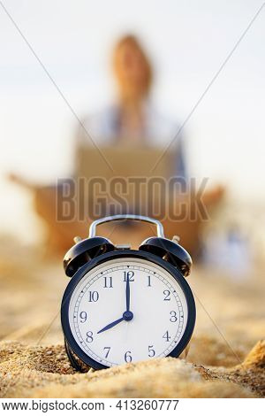 Selective Focus On The Clock. Clock On The Morning Beach, Blurred Young Woman Meditating On Backgrou