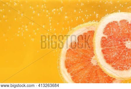 Slice Of Grapefruit In Sparkling Water On Yellow Background, Closeup With Space For Text. Citrus Sod