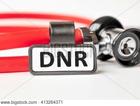 Dnr Do Not Resuscitate Lettering On A Business Card With A Holder, Next To The Red Stethoscope. Medi