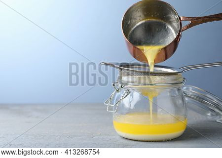 Pouring Clarified Butter Into Jar On Grey Table. Space For Text